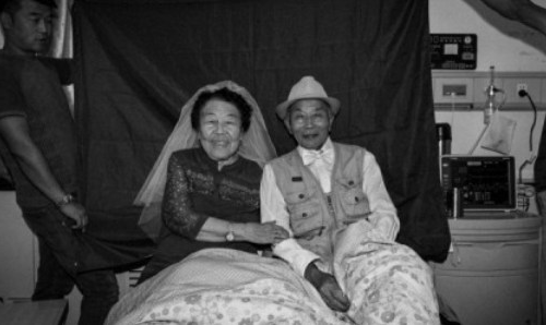 An older Chinese couple pose for the camera, smiling and linking arms with one another.