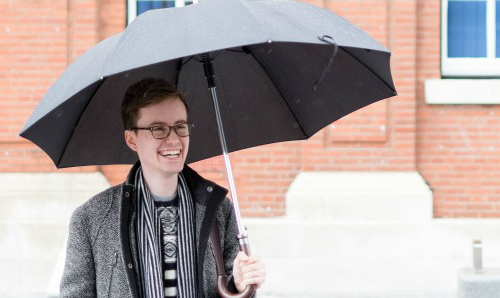 Student holding umbrella stood in rain