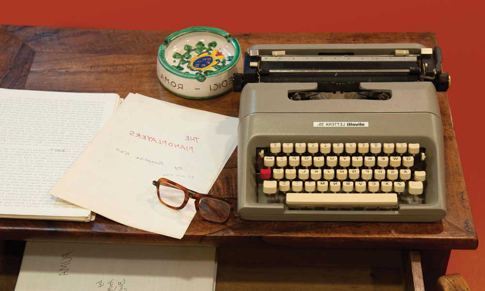 Photo of 安东尼·伯吉斯's writing desk, on top of the desk sits a typewriter, pair of glasses, 一种sh-tray and some of his written work