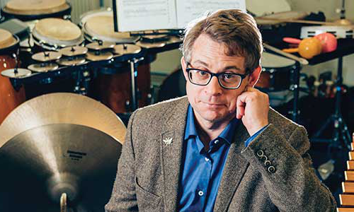 Photo of Professor Camden Reeves, surrounded by musical instruments
