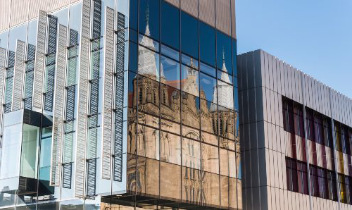 Old buildings of MG游戏官网 reflected in the windows of the modern Alan Gilbert Learning Commons building